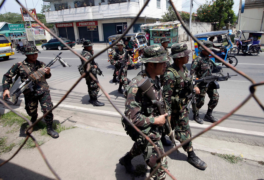 . Government troopers patrol to secure the city streets as fighting between government forces and Muslim rebels continues Saturday, Sept. 21, 2013 in Zamboanga city in southern Philippines. Government troops are battling a holdout group of Muslim rebels holding about 20 hostages. The violence in Zamboanga comes as troops search house-to-house in two neighborhoods to flush out about 30 to 40 Muslim rebels who seized scores of civilians as human shields 13 days ago when government forces repulsed their bid to occupy the port city.  (AP Photo/Bullit Marquez)