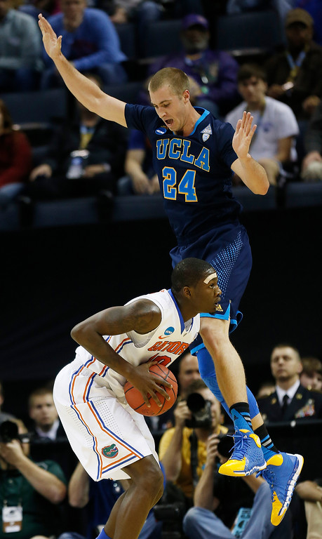 . UCLA forward Travis Wear (24) defends Florida forward Dorian Finney-Smith (10) during the first half in a regional semifinal game at the NCAA college basketball tournament, Thursday, March 27, 2014, in Memphis, Tenn. (AP Photo/John Bazemore)
