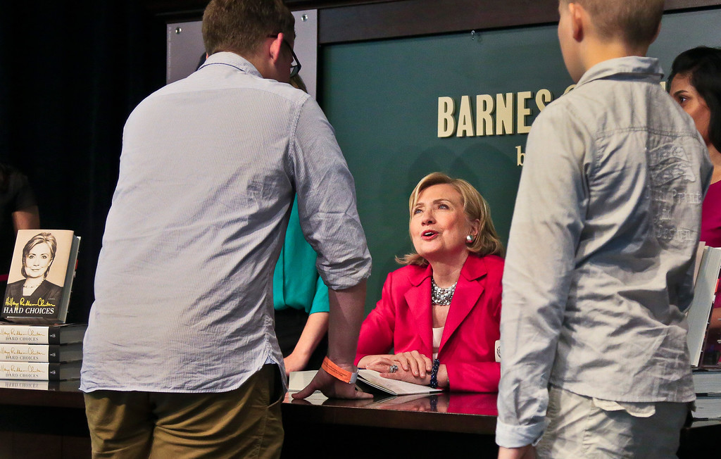 """. Joseph Rodgers, 18, left, a high school senior from Pittsburgh, Pa., chats with HiIlary Clinton, center, before receiving a signed copy of her new book  \""""Hard Choices,\"""" on Tuesday June 10, 2014, at Barnes and Noble bookstore in New York.  (AP Photo/Bebeto Matthews)"""