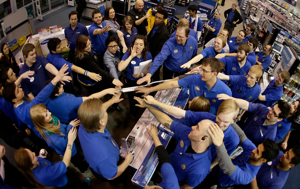 . Best Buy employees rally after a pep talk as they prepare to open the store to shoppers Thursday, Nov. 28, 2013, in Overland Park, Kan. Instead of waiting for Black Friday, which is typically the year\'s biggest shopping day, more than a dozen major retailers are opening on Thanksgiving this year. (AP Photo/Charlie Riedel)
