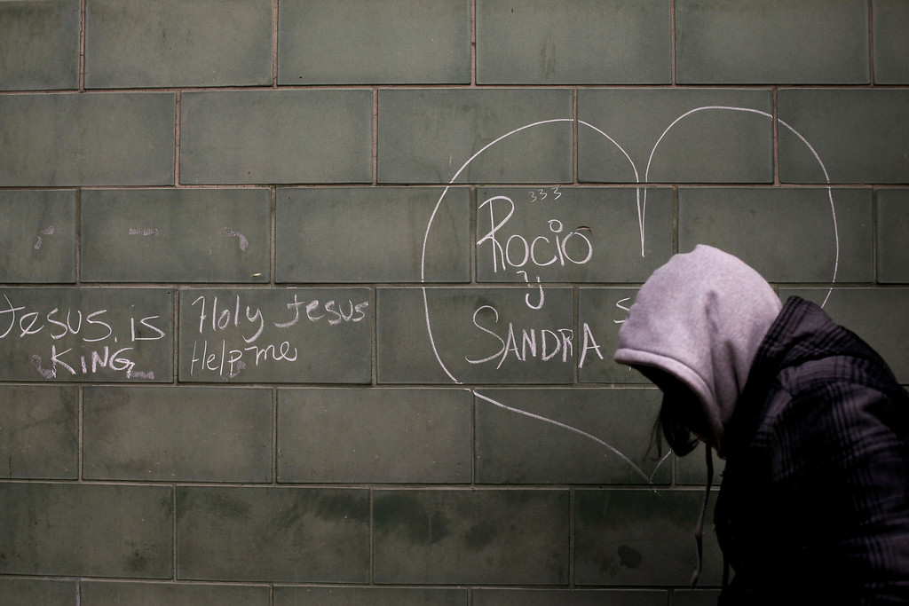 . A homeless woman walks past graffiti on a wall outside a shelter in the Skid Row section of Los Angeles, Wednesday, March 6, 2013. (AP Photo/Jae C. Hong)