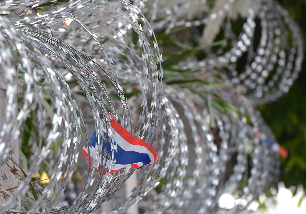 . Thai national flags hang on barbed wire during an anti-government protest at the Interior Ministry in Bangkok on November 26, 2013.  AFP PHOTO / PORNCHAI  KITTIWONGSAKUL/AFP/Getty Images