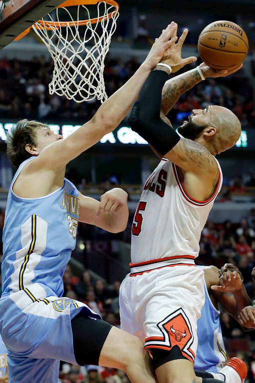 . Chicago Bulls forward Carlos Boozer, right, shoots over Denver Nuggets center Timofey Mozgov during the second half of an NBA preseason basketball game in Chicago on Friday, Oct. 25, 2013. The Bulls won 94-89. (AP Photo/Nam Y. Huh)