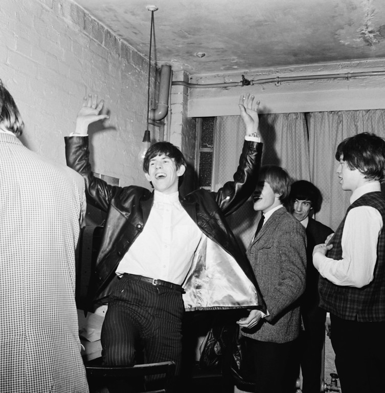 . Guitarist Keith Richards laughing with Mick Jagger, Brian Jones and Bill Wyman backstage during an early Rolling Stones tour, December 1963. (Photo by Chris Ware/Keystone Features/Getty Images)