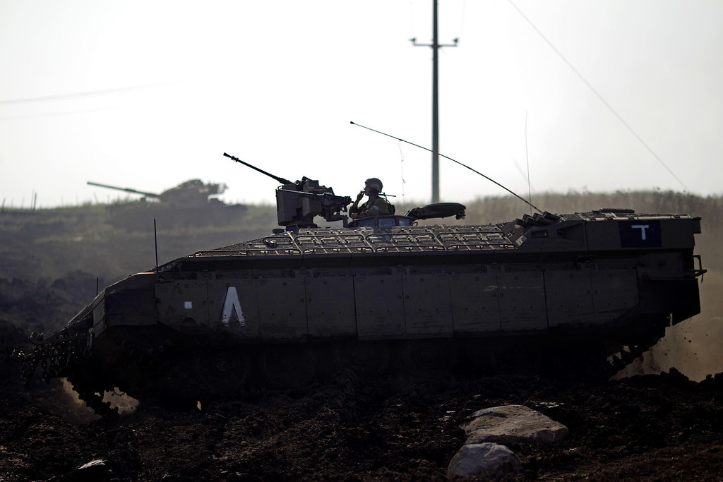 . An Israeli soldier drives an armored personal carrier during a military exercise in the Israeli controlled Golan Heights, near the border with Syria, Tuesday, May 7, 2013. (AP Photo/Ariel Schalit)