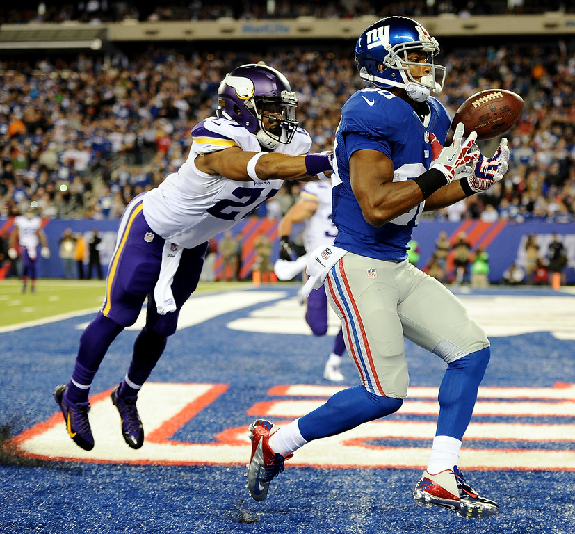 . Wide receiver Victor Cruz #80 of the New York Giants cannot control the ball as cornerback Josh Robinson #21 of the Minnesota Vikings defends during a game at MetLife Stadium on October 21, 2013 in East Rutherford, New Jersey.  (Photo by Maddie Meyer/Getty Images)