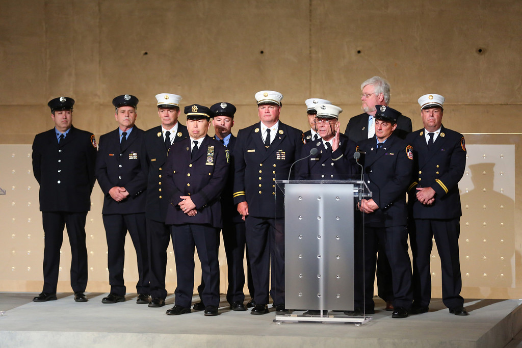 . Mickey Kross (C), who served as a Lt. in FDNY, accompanied by ten other members of FDNY and Port Authority who were trapped and survived during 9/11, speaks during the dedication ceremony at the National September 11 Memorial Museum May 15, 2014 in New York City.  (Photo by Chang W. Lee-Pool/Getty Images)