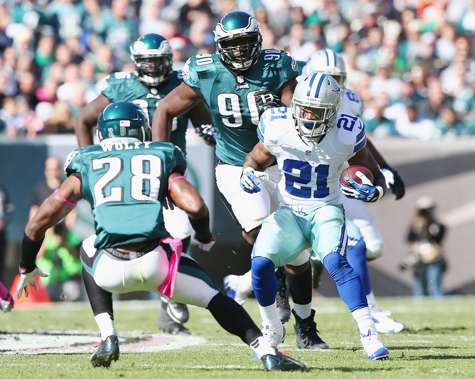 . Joseph Randle #21 of the Dallas Cowboys carries the ball as  Earl Wolff #28 and Clifton Geathers #90 of the Philadelphia Eagles defend on October 20, 2013 at Lincoln Financial Field in Philadelphia, Pennslyvania.  (Photo by Elsa/Getty Images)