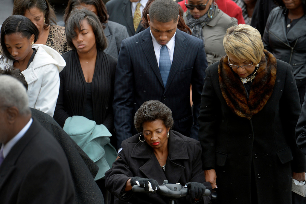 . Juanita Rogers, seated, prays with her children (l-r) Haley, Jordan and Trent during a service for her husband, former Lt. Gov. Joe Rogers, at the state Capitol in Denver, CO October 15, 2013.  (Photo By Craig F. Walker / The Denver Post)