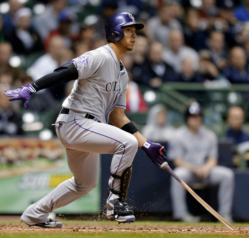 . Colorado Rockies\' Carlos Gonzalez watches his broken-bat single against the Milwaukee Brewers during the seventh inning of a baseball game Tuesday, April 2, 2013, in Milwaukee. (AP Photo/Jeffrey Phelps)
