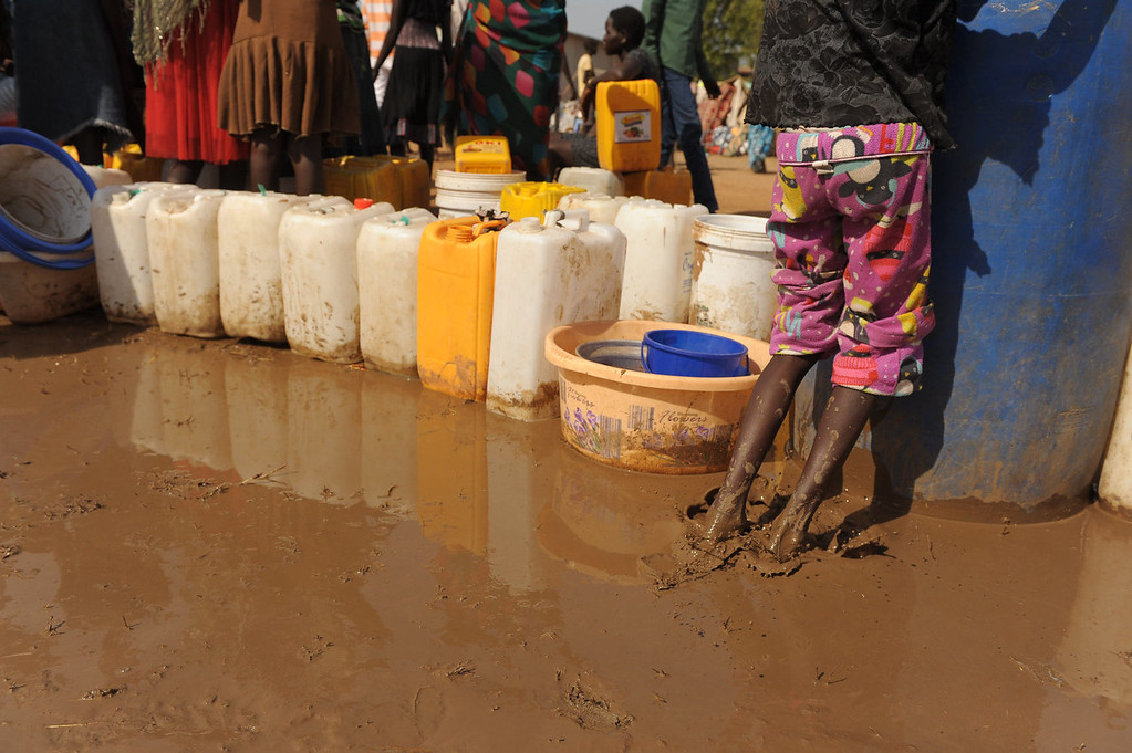 . A young South Sudanese girl plays in the mud where women have queued up their jerrycans for water being distributed from a UN reservoir at the United Nations Mission in South Sudan (UNMISS) compound in Juba on December 21, 2013 where tension remains high fueling an exodus of both local and foreign residents from the south Sudanese capital. Brutal fighting in South Sudan has reopened deep-rooted ethnic divisions, forcing tens of thousands of terrified residents to seek shelter at UN bases or flee in fear of attacks. United Nations peacekeepers are currently sheltering over 35,000 civilians in various bases across the country, many belonging to the minority ethnic group in their respective areas.   TONY KARUMBA/AFP/Getty Images