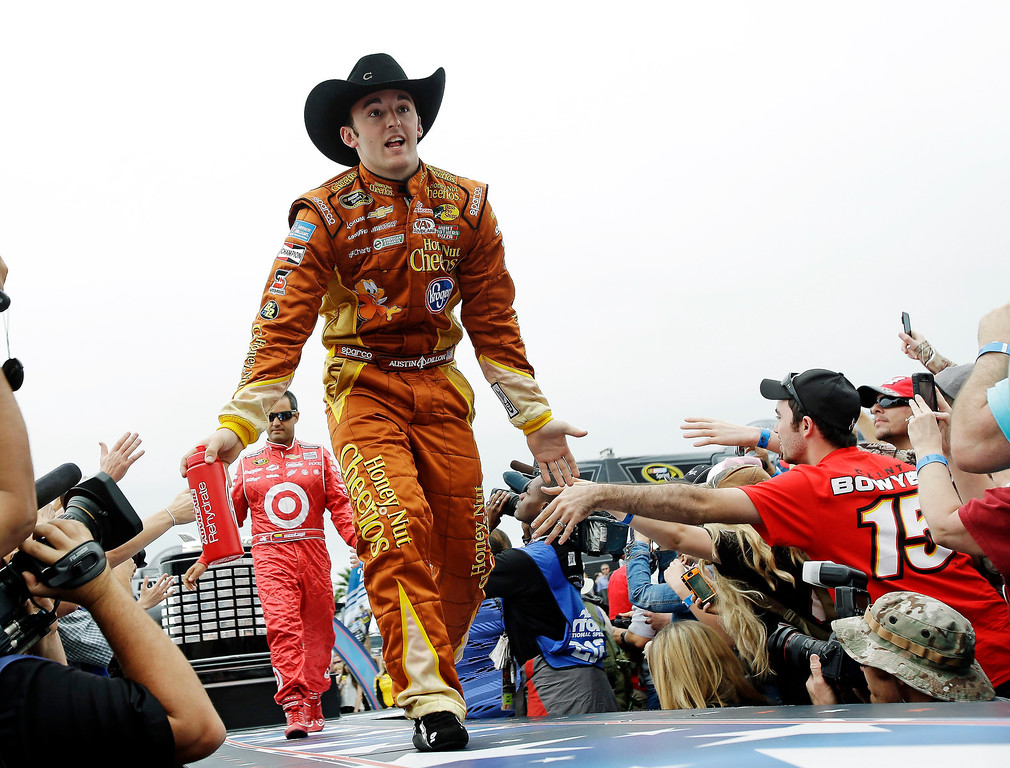. Austin Dillon, front, and Juan Pablo Montoya greet fans during driver introductions before the NASCAR Daytona 500 Sprint Cup Series auto race at Daytona International Speedway, Sunday, Feb. 24, 2013, in Daytona Beach, Fla. (AP Photo/John Raoux)