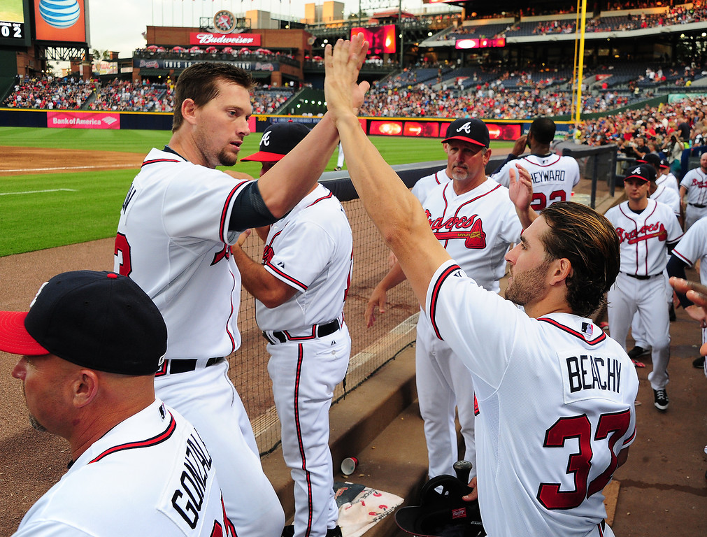 . Chris Johnson #23 of the Atlanta Braves is congratulated by Brandon Beachy #37 after scoring against the Colorado Rockies at Turner Field on July 29, 2013 in Atlanta, Georgia. (Photo by Scott Cunningham/Getty Images)
