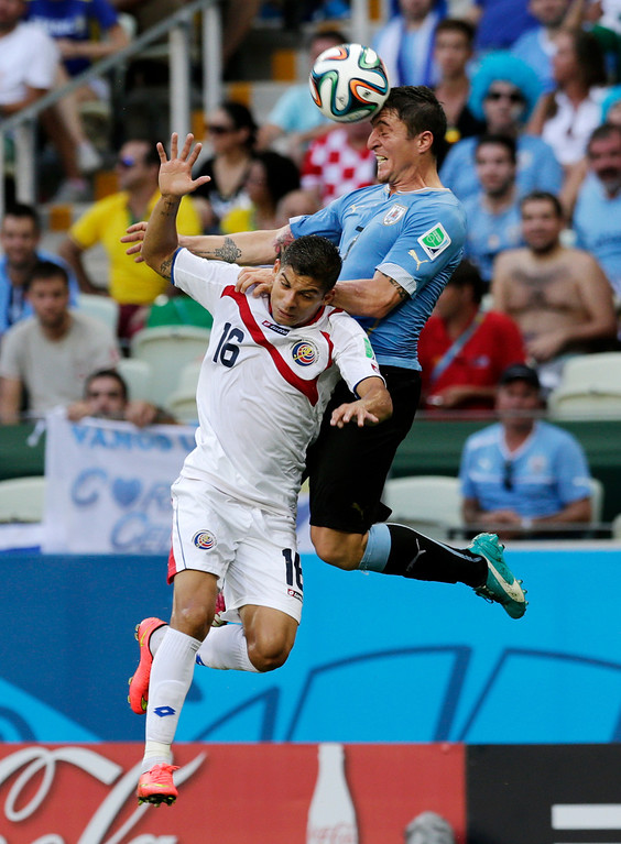 . Uruguay\'s Cristian Rodriguez heads the ball over Costa Rica\'s Cristian Gamboa (16) during the group D World Cup soccer match between Uruguay and Costa Rica at the Arena Castelao in Fortaleza, Brazil, Saturday, June 14, 2014.  (AP Photo/Fernando Llano)