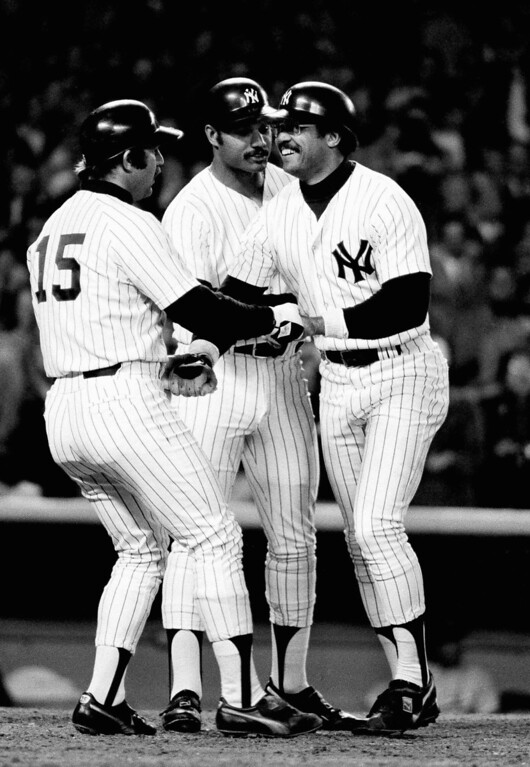 . Yankees Reggie Jackson, right, is greeted by Thurman Munson, left ,and Chris Chambliss after hitting his first homer in the fourth inning of the sixth World Series game against Dodgers at Yankee Stadium, Oct. 18, 1977. (AP Photo)