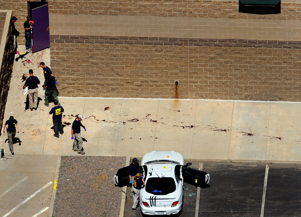 . Investigators survey the scene at the Aurora Century 16 movie theater as the suspect\'s gun lays on the concrete outside the back door to theater 9. James Holmes\' car is searched for evidence near a bloody trail left by shooting victims fleeing the building. Helen H. Richardson, The Denver Post