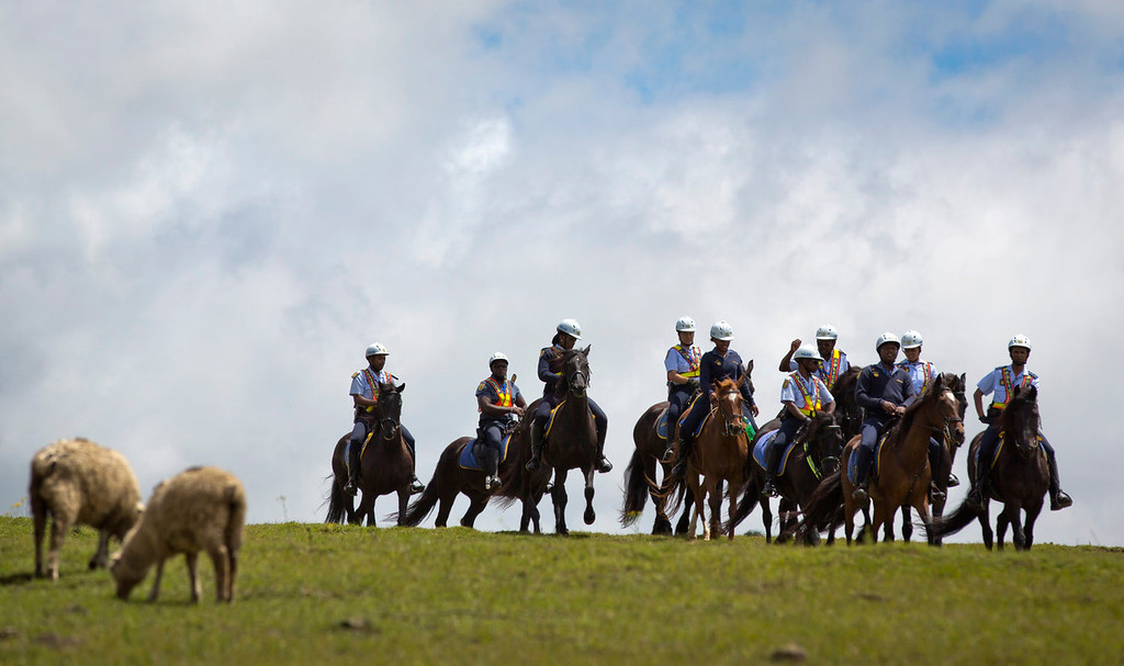 . South African mounted police patrol on a hilltop to keep public and media away from the burial site of Nelson Mandela in Qunu, South Africa Sunday, Dec. 15, 2013. (AP Photo/Ben Curtis)