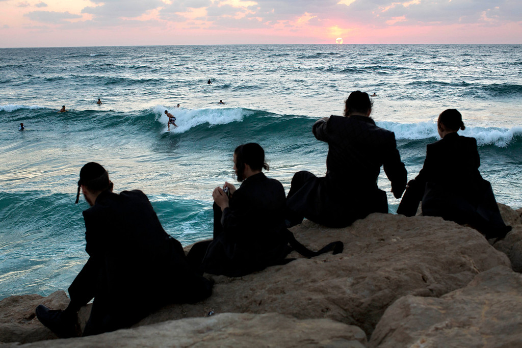 . Ultra-Orthodox Jewish men watch Israeli surfers during the Jewish holiday of Sukkot in the southern Israeli port city of Ashdod, Monday, Sept. 23, 2013.(AP Photo/Oded Balilty)