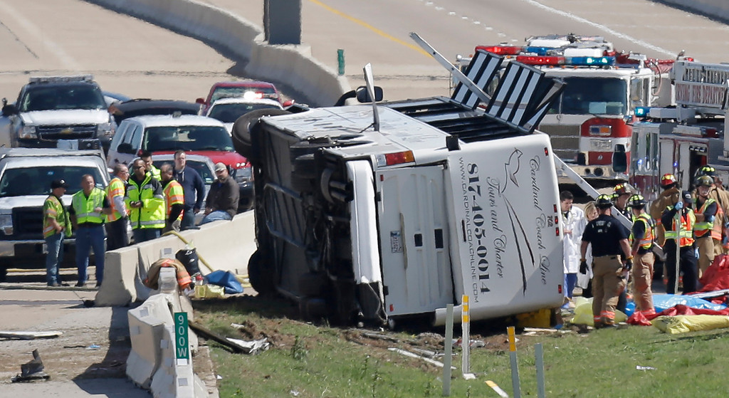 . Emergency responders works the scene of  bush crash on the George Bush Turnpike Thursday, April 11, 2013, in Irving, Texas. The chartered bus overturned on the busy highway near Dallas killing at least two people and injuring several others, authorities said. (AP Photo/LM Otero)