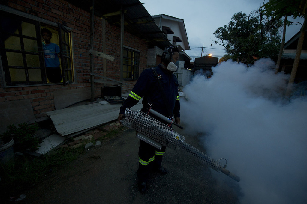. A boy (L) looks at a municipal council worker dispensing insecticide using a fogging machine among residential houses in Gombak, on the outskirt of Kuala Lumpur  on November 5, 2013. A Malaysian health official on November 4, warned citizens to take steps to eliminate mosquito breeding spots as dengue fever cases have spiked. MOHD RASFAN/AFP/Getty Images