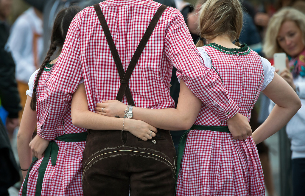 """. Visitors in bavarian style clothes pose in front of the main entrance of the Oktoberfest 2013 beer festival at Theresienwiese on September 21, 2013 in Munich, Germany. Munich\'s mayor Christian Ude will launch the Oktoberfest at 12.00 o\'clock in the Schottenhamel-tent by tapping the first barrel of beer with the traditional \""""O\'zapft is!\"""" (\""""It\'s tapped!\""""). The Munich Oktoberfest, which this year will run from September 21 through October 6, is the world\'s largest beer fest and draws millions of visitors.  (Photo by Joerg Koch/Getty Images)"""