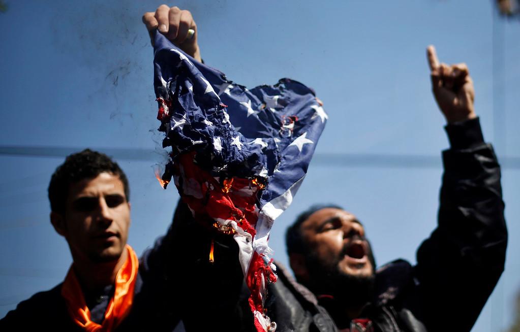 . Palestinians burn a U.S flag during a protest against the visit of U.S. President Barack Obama, in Gaza City March 20, 2013. REUTERS/Mohammed Salem