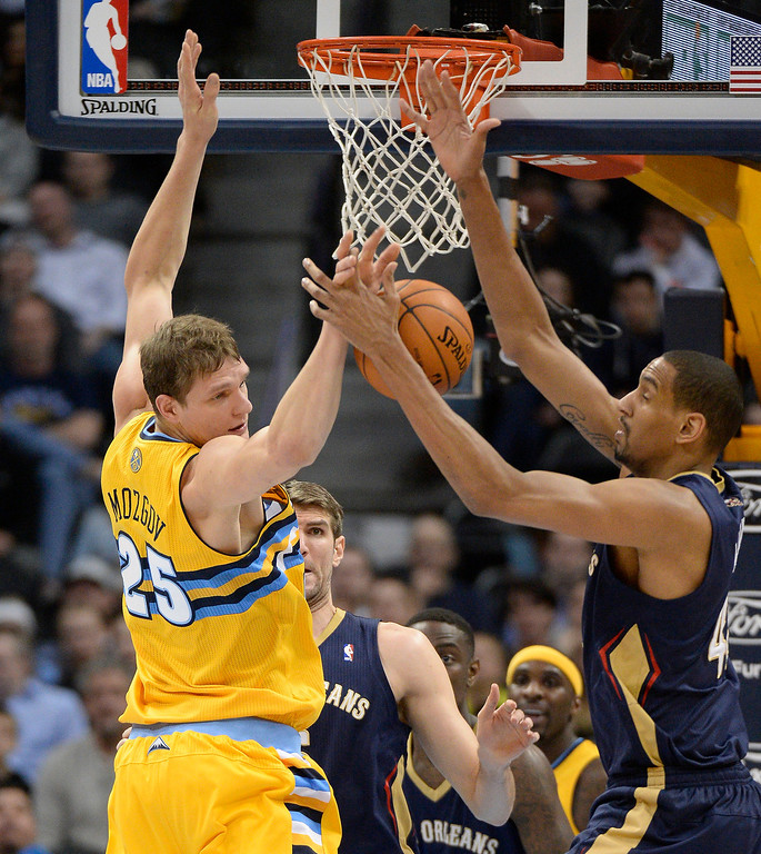 . Denver Nuggets center Timofey Mozgov (25) knocks the ball away from New Orleans Pelicans center Alexis Ajinca (42) during the first quarter April 2, 2014 at the Pepsi Center in Denver. (Photo by John Leyba/The Denver Post)