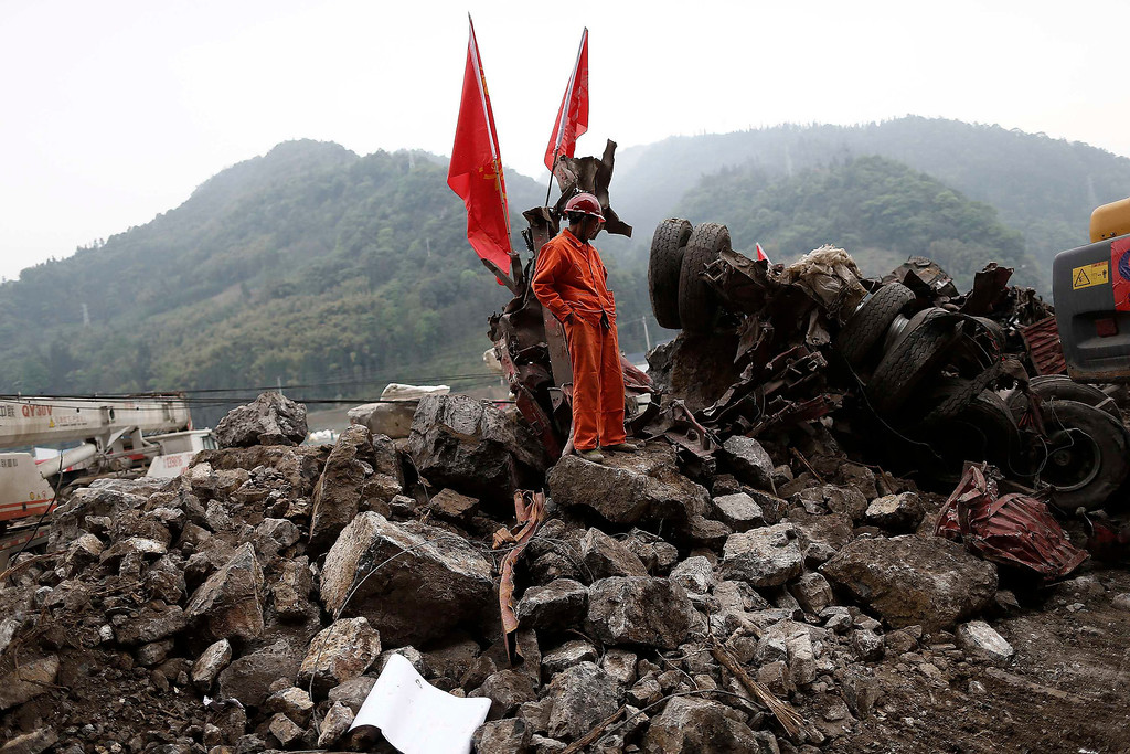 . A rescue worker stands beside a truck crushed by a landslide, after Saturday\'s earthquake, near Lingguan town of Baoxing county, Sichuan province April 22, 2013. REUTERS/Aly Song