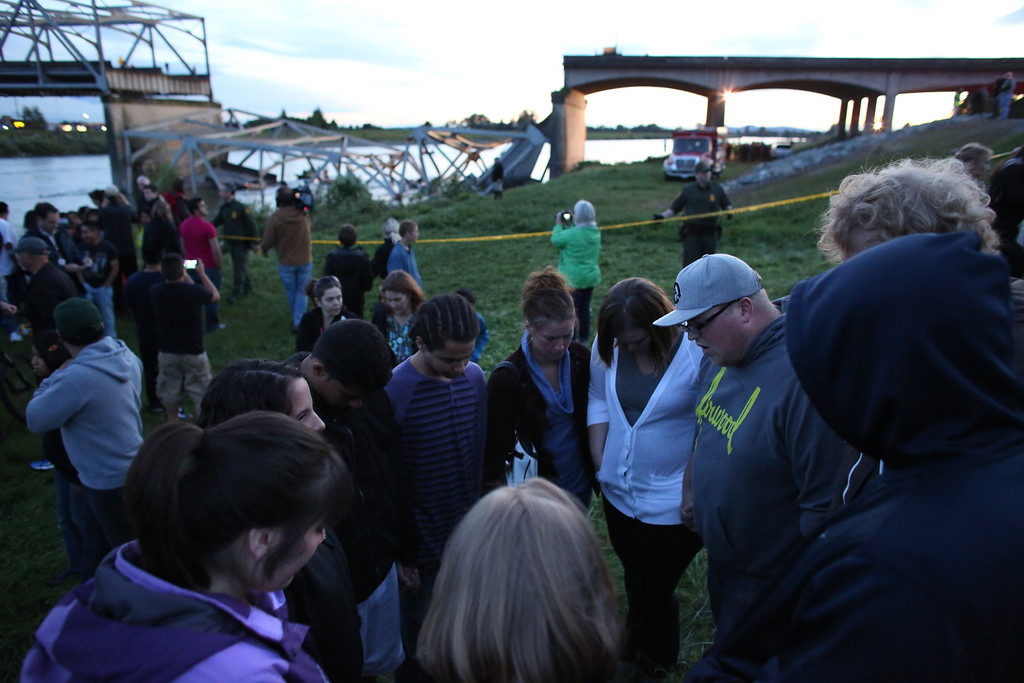 . People offer spontaneous prayer after an Interstate 5 bridge collapsed over the Skagit River between Mt. Vernon and Burlington, Wash. on Thursday, May 23, 2013. Two cars and one travel trailer went in the water. There were no know fatalities. (AP Photo/seattlepi.com, Joshua Trujillo)