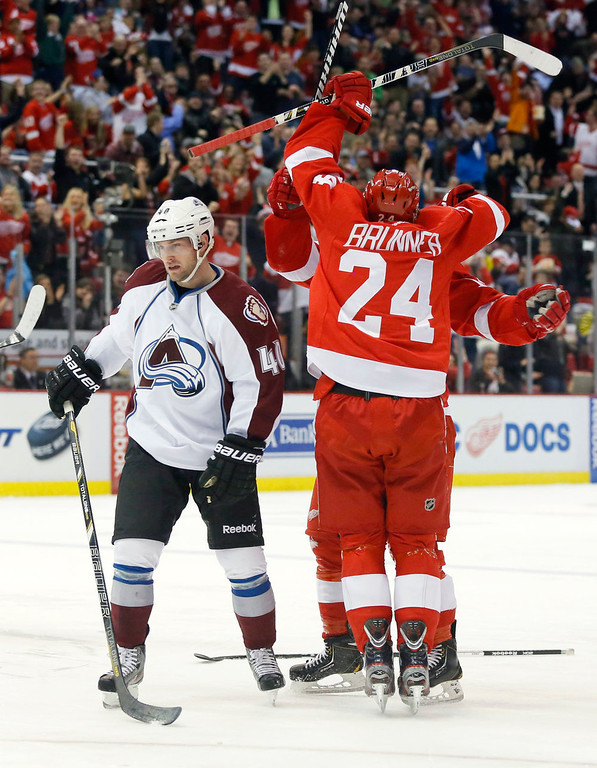 . Colorado Avalanche center Mark Olver (40) skates away as Detroit Red Wings center Damien Brunner (24) celebrates his goal with forward Gustav Nyquist, of Sweden, in the second period of an NHL hockey game Monday, April 1, 2013, in Detroit. (AP Photo/Duane Burleson)