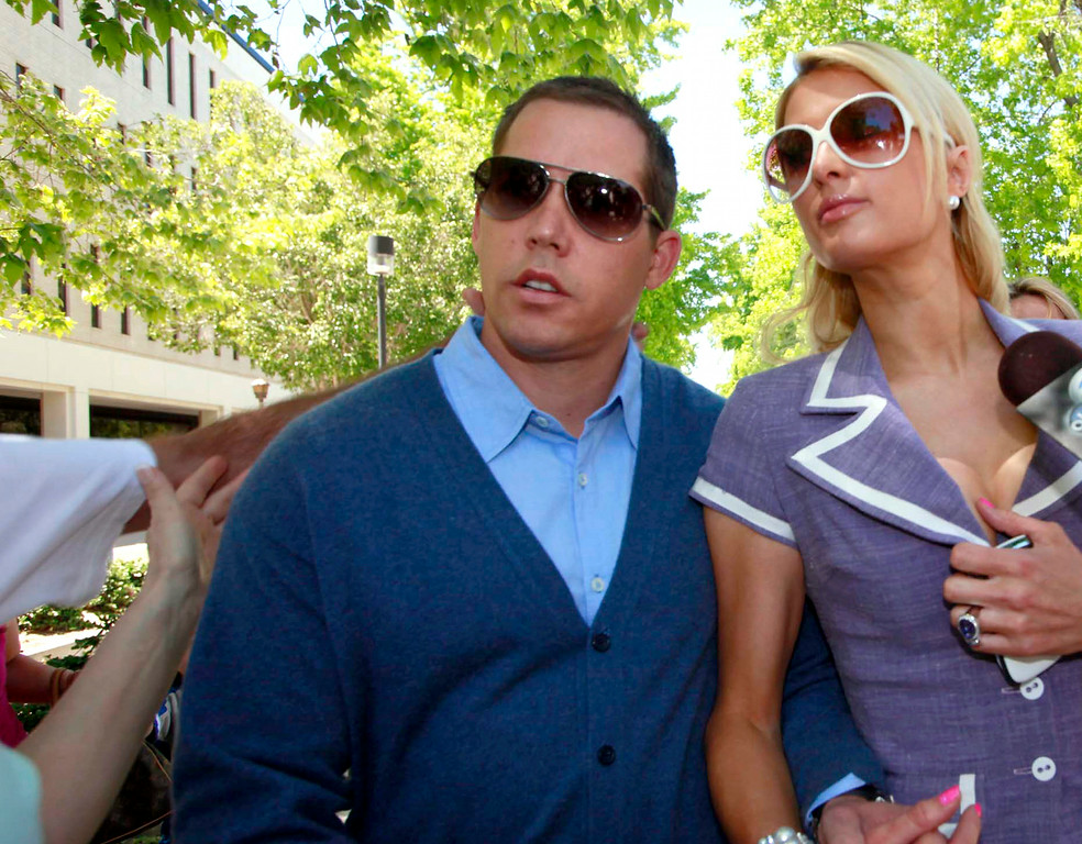 . This April 27, 2011 file photo shows an unidentified assailant\'s arm at left reaching out to grab Cy Waits, left, as he and then-girlfriend Paris Hilton arrive at court in Los Angeles. Hilton and her then-boyfriend Waits were accosted by James Rainford while they walked in to a courthouse to testify against another man who had broken in to the hotel heiress\' Hollywood Hills home. Hilton\'s security wrestled Rainford to the ground and he was promptly arrested him and he pleaded no contest to misdemeanor battery. Rainford, who was repeatedly arrested outside Hilton\'s residences and asked her to marry him, was ultimately charged with felony stalking and sentenced to probation and psychiatric counseling in April 2012. (AP Photo/Nick Ut, File)