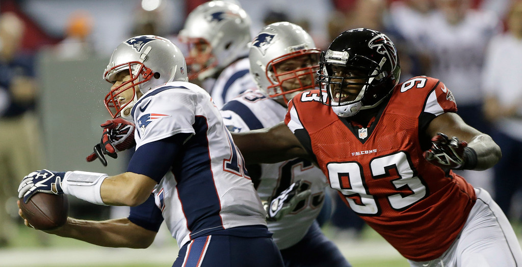 . Atlanta Falcons defensive end Malliciah Goodman (93) tries to tackle New England Patriots quarterback Tom Brady (12) during the first half of an NFL football game, Sunday, Sept. 29, 2013, in Atlanta. (AP Photo/John Bazemore)
