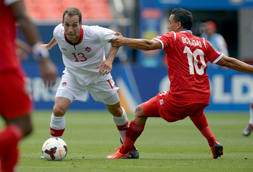 . Eybir Bonaga #10 of Panama grabs ahold of Pedro Pacheco Melo #13 of Canada as he controls the ball during the first half of the CONCACAF Gold Cup soccer game July 14, 2013 at Sports Authority Field at Mile High. (Photo By John Leyba/The Denver Post)