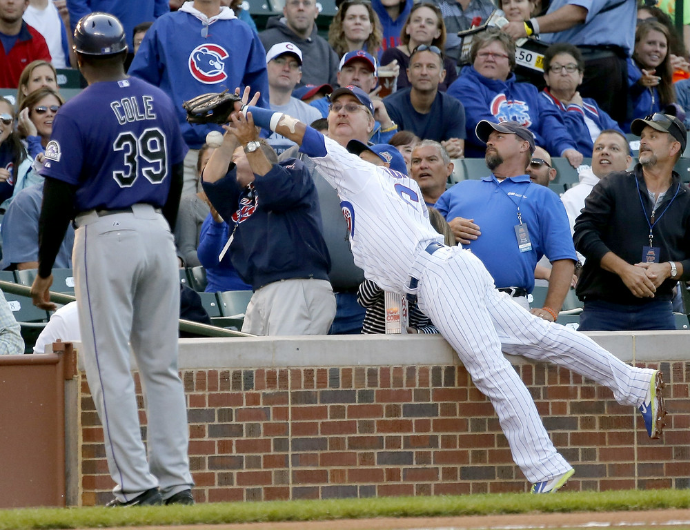 . Chicago Cubs third baseman Emilio Bonifacio is unable to catch a fly ball in foul territory by Colorado Rockies\' Charlie Blackmon, as third base coach Stu Cole watches, during the first inning of a baseball game Monday, July 28, 2014, in Chicago. (AP Photo/Charles Rex Arbogast)