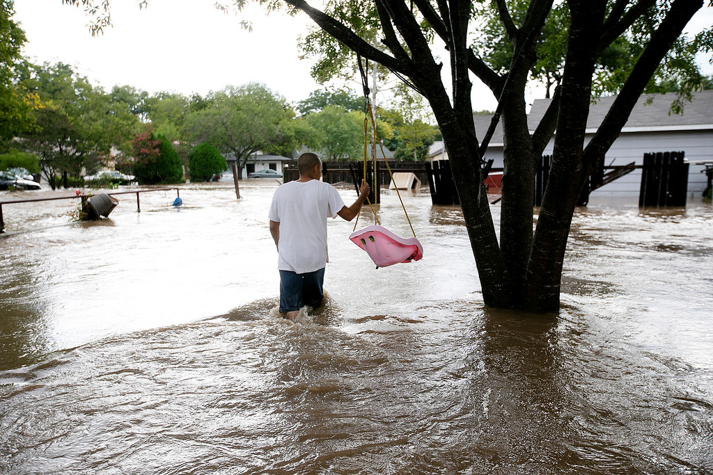 . Alejandro Salazar holds on to a swing as he watches the flood waters move on Canella Drive in Austin, Texas, on Thursday, Oct. 31, 2013. Heavy overnight rains brought flooding to the area. (AP Photo/Austin American-Statesman, Deborah Cannon)