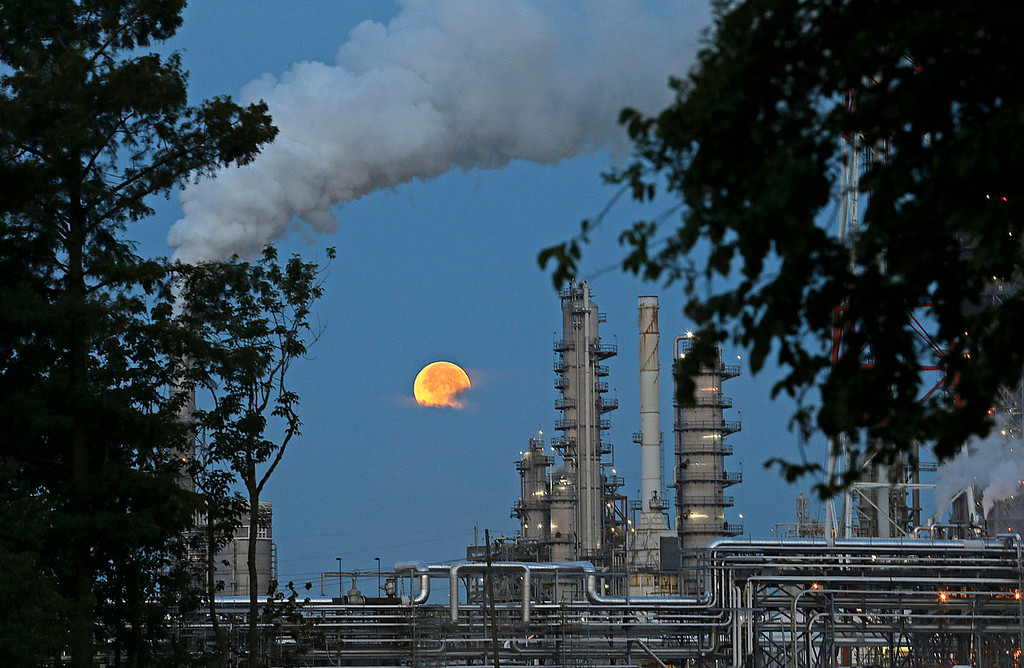 ". The larger-than-normal full moon referred to as a ""super moon\"" is seen setting beyond a refinery in Norco, Louisiana on Sunday, June 23, 2013. The larger than normal moon called a \""super moon\"" happens only once this year as the moon on its elliptical orbit is at its closest point to earth and is 13.5 percent larger than usual.  (AP Photo/Gerald Herbert)"