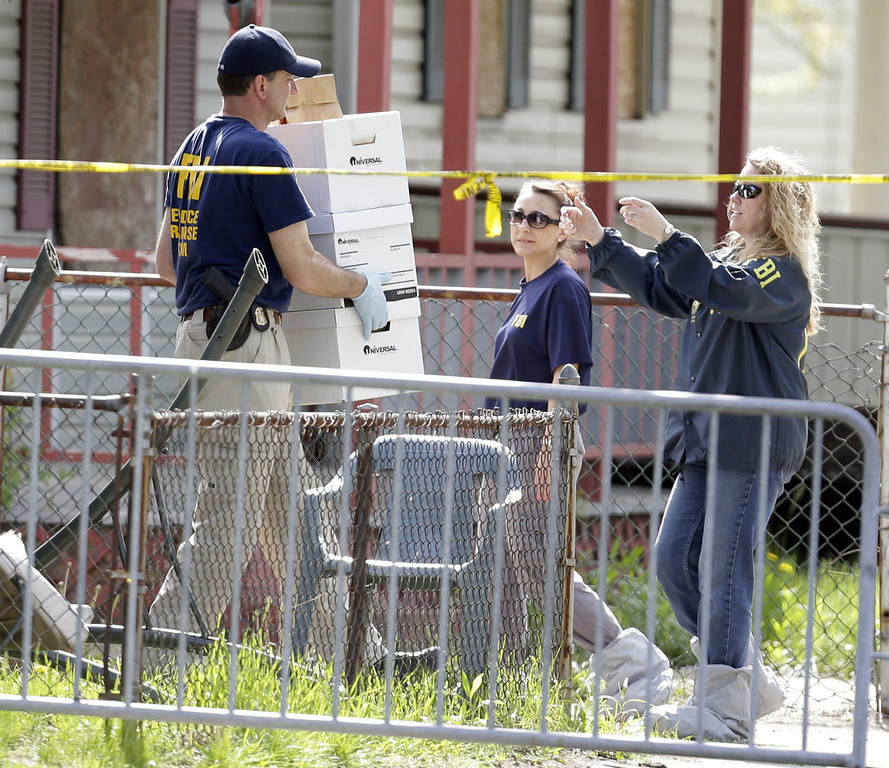 . Law enforcement officials gather evidence at the crime scene where three women were held captive in Cleveland, Ohio, Thursday, May 9, 2013.  Ariel Castro, a 52-year-old former school bus driver, is being held on $8 million bail under a suicide watch in jail, where he is charged with rape and kidnapping for allegedly abducting three women and holding them captive in his home for a decade.  (AP Photo/David Duprey)