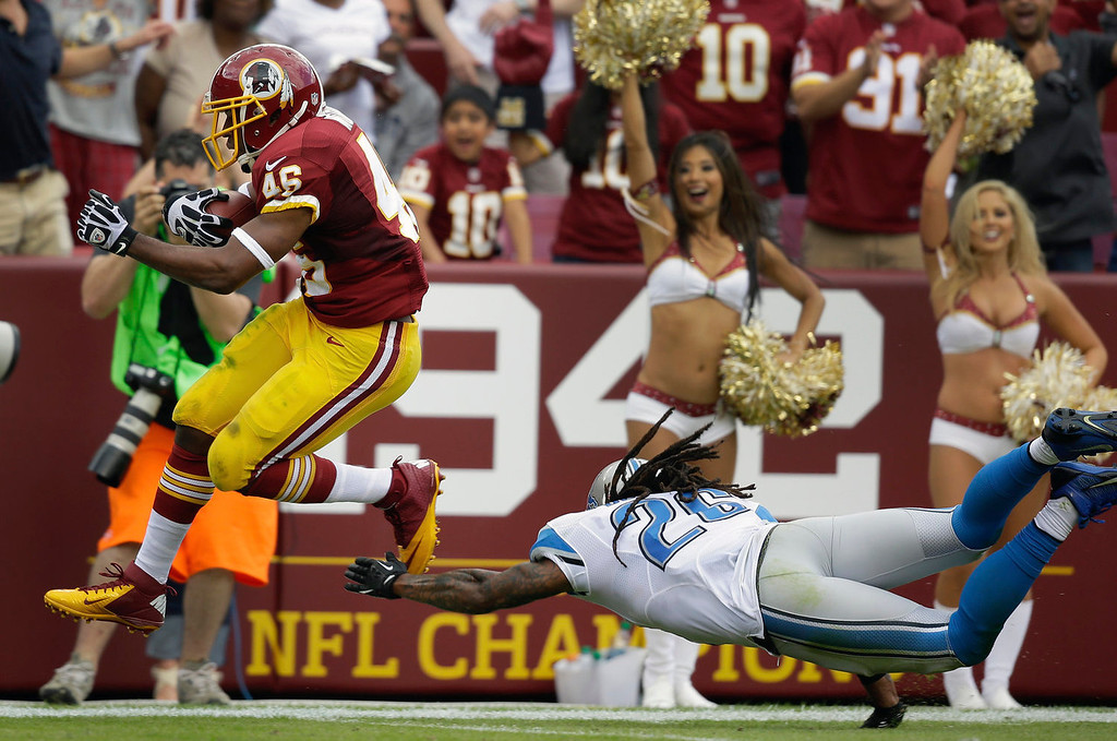 . Washington Redskins running back Alfred Morris escapes the diving grasp of Detroit Lions free safety Louis Delmas to score a touchdown during the first half of a NFL football game in Landover, Md., Sunday, Sept. 22, 2013. (AP Photo/Alex Brandon)
