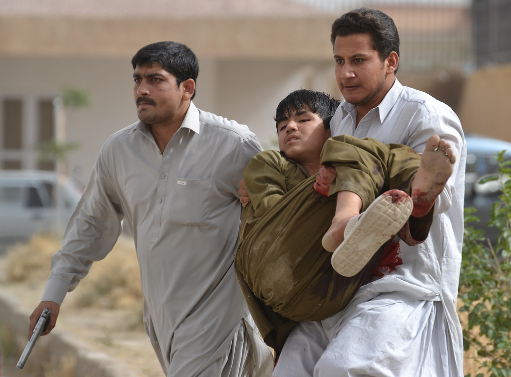 . A Pakistani man carries an injured boy after militants attacked a hospital in Quetta, the capital of Baluchistan province, on June 15, 2013.  AFP PHOTO/ Banaras KHAN/AFP/Getty Images
