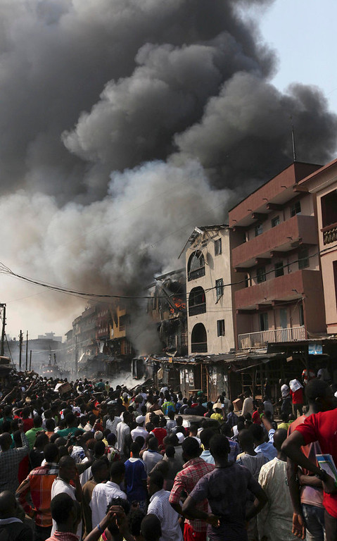. People gather at the site of a  a fire at a warehouse on Lagos Island in Lagos, Nigeria, Wednesday, Dec. 26, 2012. An explosion ripped through a warehouse Wednesday where witnesses say fireworks were stored in Nigeria\'s largest city, sparking a fire. It wasn\'t immediately clear if anyone was injured in the blast that firefighters and locals struggled to contain. (AP Photos/Sunday Alamba)