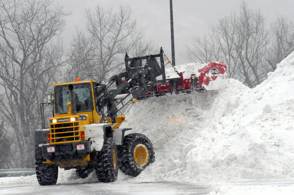 . J & R Landscaping, of Keyser, W.Va., uses a front end loader to move snow in a Wal Mart parking lot Tuesday, Jan. 21, 2014, in Cumberland, Md. (AP Photo/Cumberland Times-News, Steven Bittner)