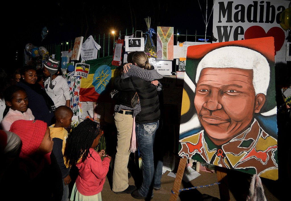 . People stand near portraits of Nelson Mandela and messages left for him outside the Medi Clinic Heart hospital in Pretoria on June 26, 2013. Emotional crowds gathered outside the hospital where Nelson Mandela lay in critical condition on June 26, 2013, as relatives and clan elders made preparations for the revered former South African leader\'s final journey. Singing supporters amassed outside the Pretoria hospital where the 94-year-old anti-apartheid hero was fighting for his life. FILIPPO MONTEFORTE/AFP/Getty Images