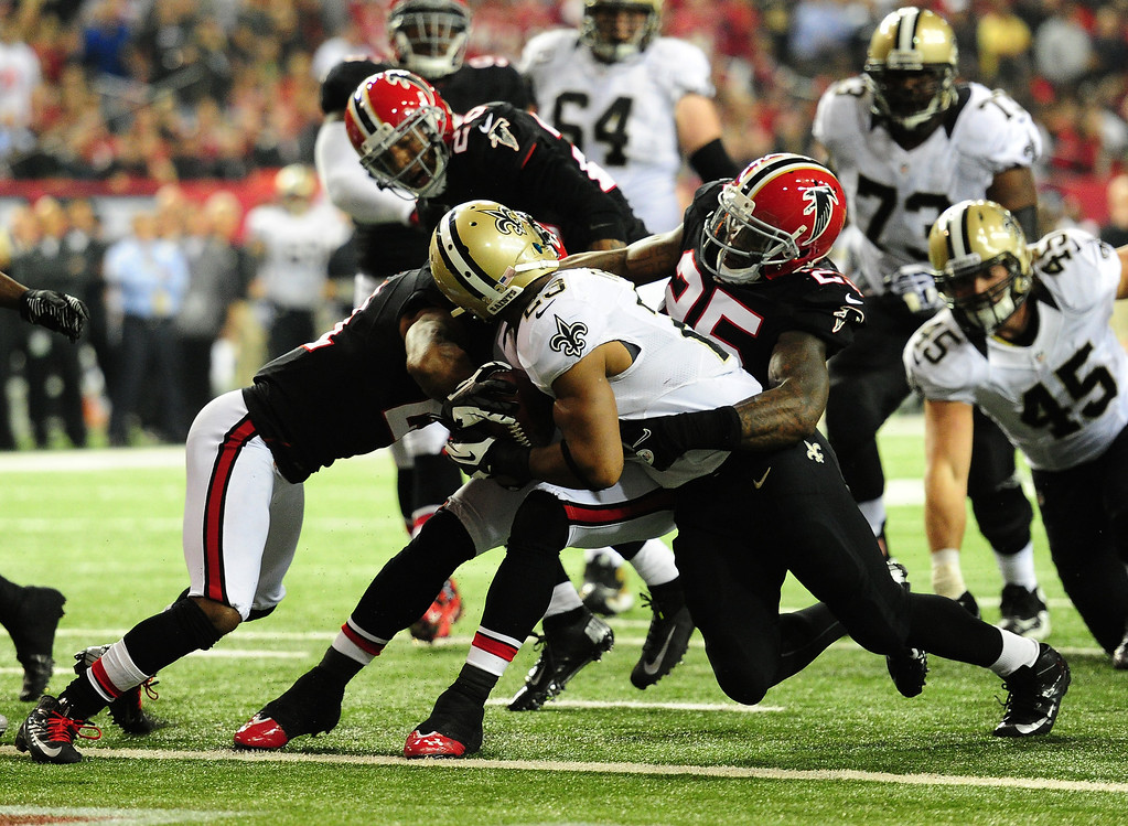 . ATLANTA, GA - NOVEMBER 18:  Pierre Thomas #23 of the New Orleans Saints has his face mask pulled by William Moore #25 of the Atlanta Falcons at the Georgia Dome on November 29, 2012 in Atlanta, Georgia  (Photo by Scott Cunningham/Getty Images)