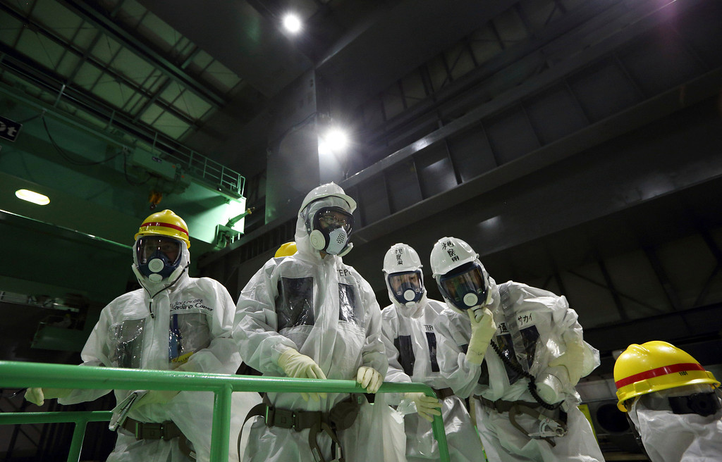. Members of the media wearing protective suits and masks look at the spent fuel pool from a fuel handling machine inside the building housing the Unit 4 reactor at the Fukushima Dai-ichi nuclear power plant in Okuma, Fukushima Prefecture, Japan, Thursday, Nov. 7, 2013. Japanese regulators on Oct. 30 formally approved the removal of fuel rods from the cooling pool at the damaged Unit 4 reactor building considered the highest risk at the crippled nuclear plant. Removing the fuel rods is the first major step in a decommissioning process that is expected to last decades at the Fukushima plant, where three reactors melted down after the March 2011 earthquake and tsunami. (AP Photo/Tomohiro Ohsumi, Pool)