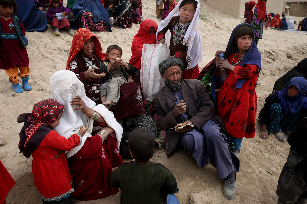 . In this Sunday, May 4, 2014 photo, Survivors wait to receive donations near the site of Friday\'s landslide that buried Abi-Barik village in Badakhshan province, northeastern Afghanistan. Stranded and with no homes, many of the families have struggled to get aid. Some have gone to nearby villages to stay with relatives or friends. (AP Photo/Massoud Hossaini)