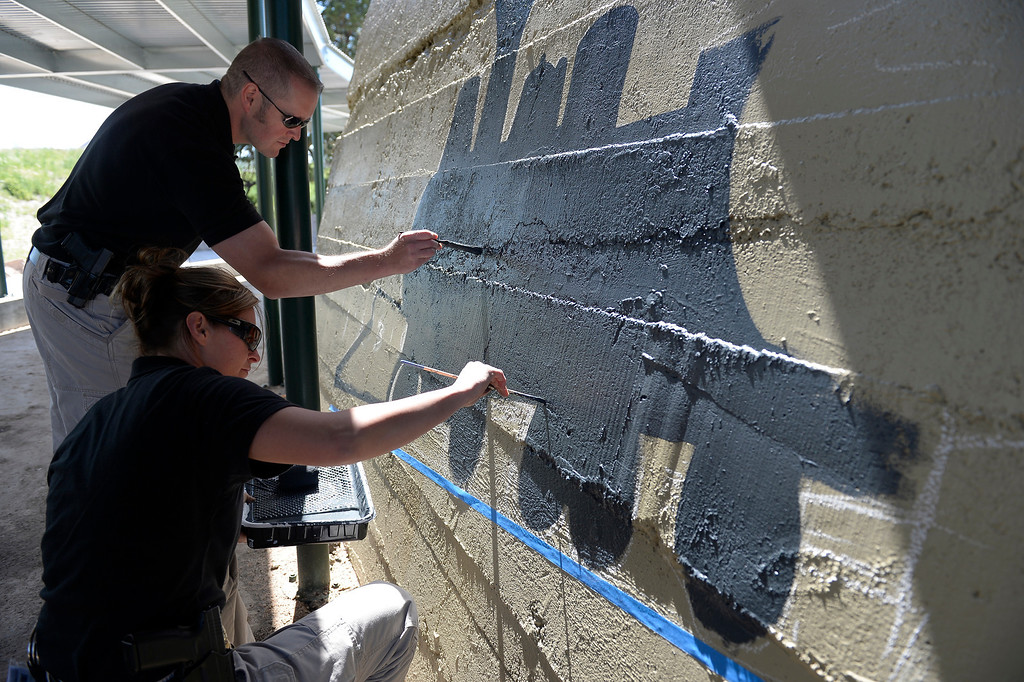 . Castle Rock police officer Renee Tremaine and Special Operations Seth Morrissey paint at Hangmans Gulch underpass June 9, 2014 along the Plum Creek trail. They plan on painting murals at 12 underpasses throughout the town, hoping to discourage graffiti in the area. (Photo by John Leyba/The Denver Post)