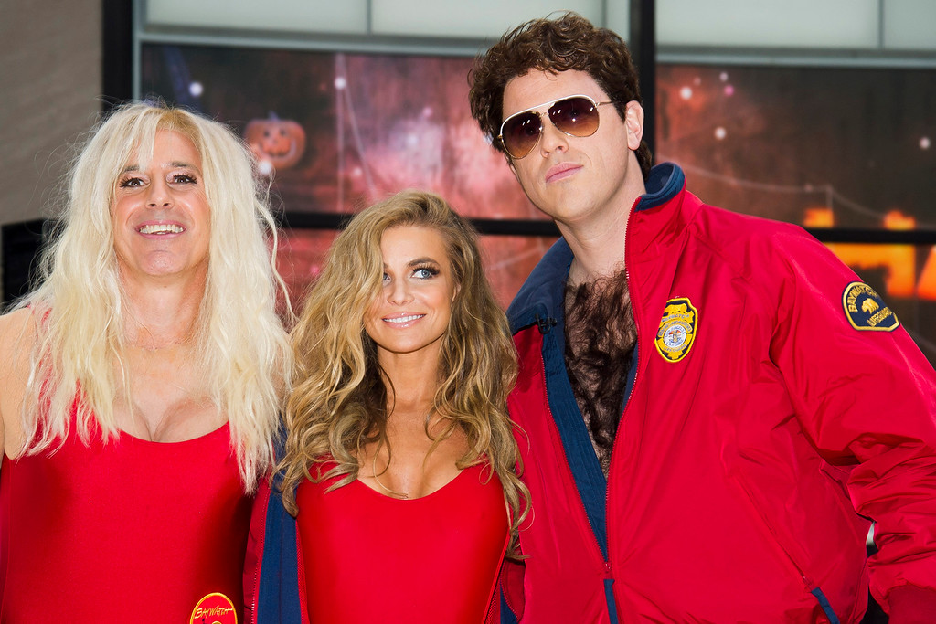 """. Former \""""Baywatch\"""" star Carmen Electra, center, poses with Matt Lauer, left, dressed as Pam Anderson\'s character C.J. Parker, and Willie Geist, right, dressed as David Hasselhoff,\'s character Mitch Buchannon on NBC\'s \""""Today\"""" Halloween show on Thursday, Oct. 31, 2013 in New York. (Photo by Charles Sykes/Invision/AP)"""