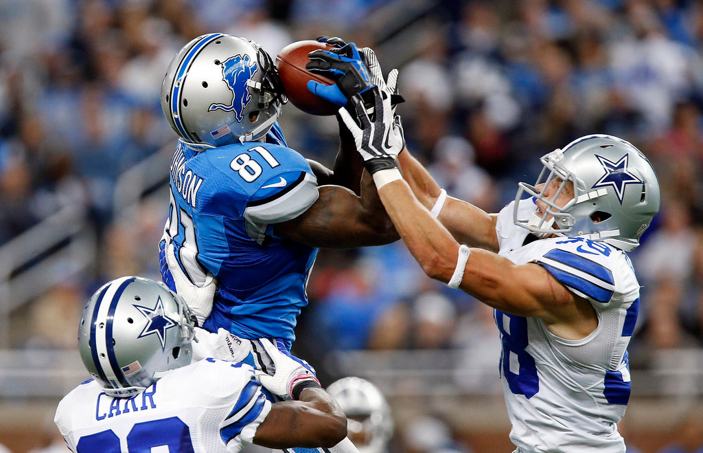 . Detroit Lions wide receiver Calvin Johnson (81) pulls in a 54-yard reception as Dallas Cowboys cornerback Brandon Carr (39) and Dallas Cowboys defensive back Jeff Heath (38) defends in the fourth quarter of an NFL football game in Detroit, Sunday, Oct. 27, 2013. (AP Photo/Duane Burleson)