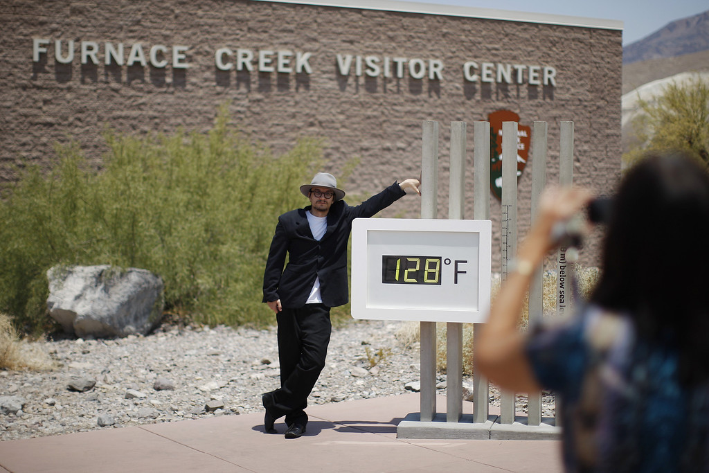 . Kevin Martin of Corona, California poses for a snapshot by an unofficial thermometer reading at Furnace Creek Visitor Center reading 128 degrees as a heat wave spreads across the American West on June 30, 2013 in Death Valley National Park, California.    (Photo by David McNew/Getty Images)