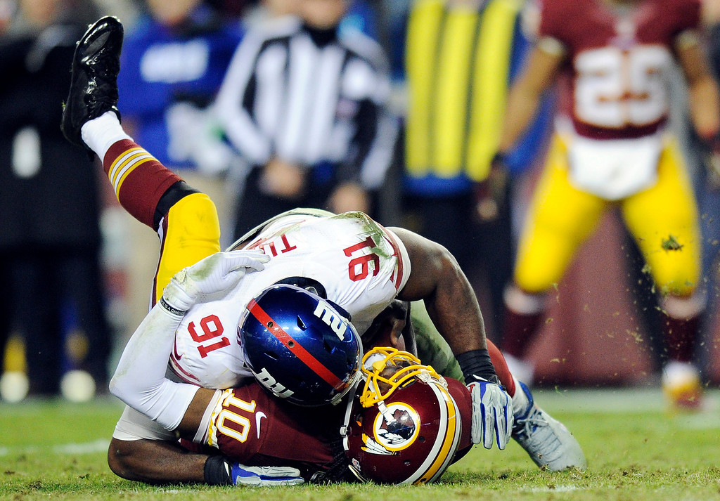 . Washington Redskins quarterback Robert Griffin III (10) is sacked by New York Giants defensive end Justin Tuck (91) during the second half of an NFL football game Sunday, Dec. 1, 2013, in Landover, Md. The Giants won 24-17. (AP Photo/Nick Wass)